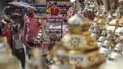 """Keluarga Mesir melihat lentera tradisional yang dikenal dalam bahasa Arab sebagai """"Fanous"""" yang dijual selama bulan suci Ramadan di Sayeda Zainab, Kairo, 17 April 2020.  Menjelang Ramadan 1441 H, warga Mesir mulai berburu lentera warna-warni di tengah pandemi corona Covid-19. (Mohamed el-Shahed/AFP)"""