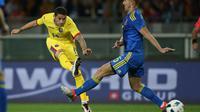Gelandang Rumania, Nicolae Stanciu (kiri) melakukan tembakan ke arah gawang Ukraina (29/5/2016). Stanciu diprediksi bakal menjadi bintang muda yang menonjol pada Euro 2016.  (AFP/Marco Bertorello)