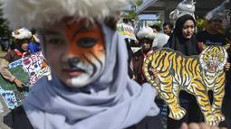 Sejumlah pelajar membawa gambar harimau saat melakukan aksi demonstrasi dalam peringatan Hari Bumi Sedunia di Banda Aceh (22/4). Mereka menyerukan penyelamatan empat satwa kunci yang terancam punah. (AFP Photo/Chaideer Mahyuddin)