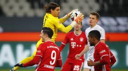 Kiper Borussia Moenchengladbach, Yann Sommer menangkap bola dari ancaman striker Bayern Munich, Robert Lewandowski (kiri) dalam laga lanjutan Liga Jerman 2020/21 pekan ke-15 di Borussia Park, Jumat (8/1/2021). Moenchengladbach menang 3-2 atas Bayern Munich. (AFP/Wolfgang Rattay/Pool)