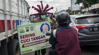 Polisi memakai helm bertema virus corona COVID-19 saat melakukan kampanye dan penyemprotan disinfektan kepada pengendara di Mojokerto, Jawa Timur, Jumat (3/4/2020). Aksi ini dilakukan sebagai tindakan pencegahan penyebaran virus corona COVID-19. (JUNI KRISWANTO/AFP)