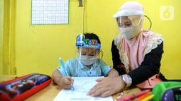 Guru menggunakan face shield saat mengajari murid di Taman Pendidikan Al-Qur'an (TPA) Al-Muthmainnah Cinere, Depok, Rabu (1/7/2020). Jadwal murid diatur dalam beberapa sesion waktu (pagi siang sore) sebagai wajud penerapan sosial distancing dalam kelas. (merdeka.com/Arie Basuki)