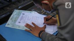 Petugas Satpol PP mendata warga yang tidak menggunakan masker di kawasan Pasar Baru, Jakarta, Jumat (21/8/2020). Sanksi tersebut dilakukan sebagai bagian dari upaya pencehagan penyebaran virus covid-19. (Liputan6.com/Immanuel Antonius)