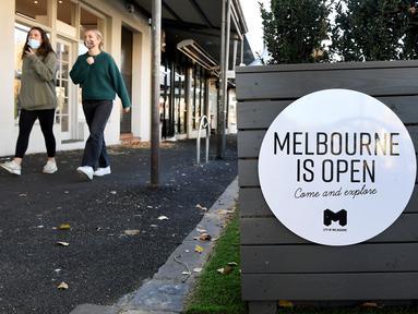 Orang-orang berjalan melewati tanda di kafe dan restoran Lygon Street di Melbourne, Rabu (2/6/2021). Kota Melbourne dan wilayah lainnya di negara bagian Victoria, Australia, akan mengalami perpanjangan lockdown yang tadinya dijadwalkan berakhir pada Kamis (3/6/2021) malam. (William WEST / AFP)
