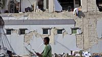 Seorang pria berjalan melewati bangunan yang rusak akibat gempa di Mamuju, Sulawesi Barat, Indonesia, Senin (18/1/2021). Jumlah warga yang mengungsi usai gempa magnitudo 6,2 di Sulawesi Barat mencapai 19.435 orang. (AP Photo/Yusuf Wahil)