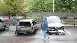 Pejalan kaki melintasi mobil yang hangus terbakar oleh orang tak dikenal di kota Gothenburg, Swedia, Selasa (14/8). Aksi vandalisme besar-besaran ini juga terjadi menjelang pemilu yang digelar pada 9 September ini. (Henrik BRUNNSGARD/TT News Agency/AFP)