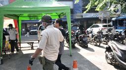 Petugas Satpol PP saat menjaring salah seorang warga yang tidak mengenakan masker di area Pasar Kramat Jati, Jakarta, Rabu (17/6/2020). Bagi pelanggar aturan PSBB juga diberikan sanksi hukuman sosial membersihkan jalanan guna meningkatkan kedisiplinan warga. (merdeka.com/Iqbal S. Nugroho)