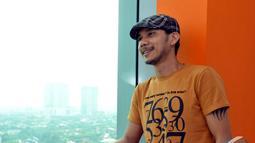 Norman Kamarau tampil santai dengan mengenakan kaos orange, celana jeans dan topi, Jakarta. Foto diambil pada Jumat (21/11/2014). (Liputan6.com/Panji Diksana)