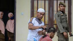 Seorang anak Punk dicukur rambutnya oleh petugas kepolisian di Banda Aceh (9/1). Indonesia merupakan negara yang memiliki populasi punk terbesar di dunia. (AFP Photo/Chaideer Mahyuddin)