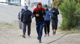 Para pria melakukan jogging sebelum bermain sepak bola di lapangan tanah sebelum buka puasa selama bulan Ramadhan, di ibu kota Libya, Tripoli (24/4/2021). (AFP/Mahmud Turkia)