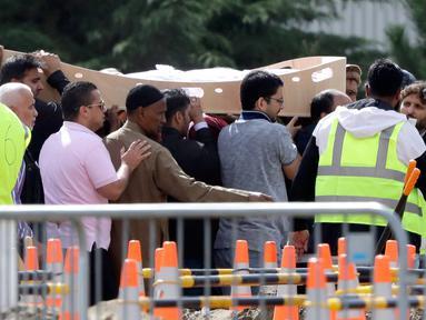 Pelayat membawa jenazah korban penembakan masjid untuk dimakamkan di Memorial Park Cemetery, Christchurch, Selandia Baru, Rabu (20/3). Keluarga korban mulai memakamkan korban penembakan masjid di Christchurch. (AP Photo/Mark Baker)