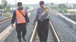 Petugas gabungan dari Polsuska dan Babinkamtibmas Kemijen Semarang memeriksa rel kereta api dan alat pemindah jalur kereta di Jalur Kemijen, Minggu (3/6). Pemeriksaan untuk pengamanan jalur kereta api jelang arus mudik lebaran. (Liputan6.com/Gholib)