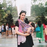 Kehadiran anak pertamanya ini menjadi momen paling membagiakan bagi Momo Geisha, salah satu momen unik terjadi saat Momo menggendong si buah hatinya dengan kain jarik saat berada di Bandara Singapore. (Liputan6.com/IG/@therealmomogeisha)