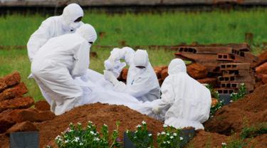 Paramedis memakai pakaian pelindung saat menguburkan jenazah yang tewas akibat virus Nipah di Kozhikode, Kerala, India Selatan, Kamis (24/5). Langkah tersebut dilakukan untuk mencegah penularan virus Nipah. (AP Photo/K.Shijith)