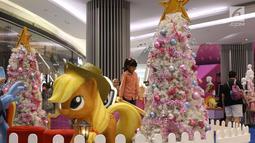 Seorang anak bermain di dekat pohon Natal di Lippo Mal Puri, Jakarta, Jumat (22/12). Jelang Natal banyak pusat perbelanjaan mendekor bangunannya bernuansa natal untuk menarik daya tarik minat masyarakat. (Liputan6.com/Angga yuniar)