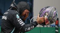 Pembalap Mercedes Lewis Hamilton dari Inggris menangis setelah memenangkan Grand Prix Formula Satu Turki di arena pacuan kuda Istanbul Park di Istanbul, Minggu (15/11/2020). (AP Photo/Kenan Asyali, Pool)