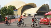 Wisatawan bersepeda mengelilingi obyek wisata Taman Mini Indonesia Indah (TMII) di Jakarta, Minggu (21/6/2020). Setelah tidak beroperasi akibat pandemi, pengelola membuka kembali TMII dengan menerapkan protokol kesehatan pencegahan COVID-19 dan pembatasan pengunjung. (Liputan6.com/Immanuel Antonius)