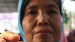 Warga menunjukkan kartu Keluarga Sejahtera saat penerima dana Program Keluarga Harapan (PKH) tahap 3 di Desa Cikuya Kabupaten Tanggerang, Jumat (28/9). Sebanyak 350 keluarga menerima dana manfaat PKH. (Liputan6.com/HO/Agus)