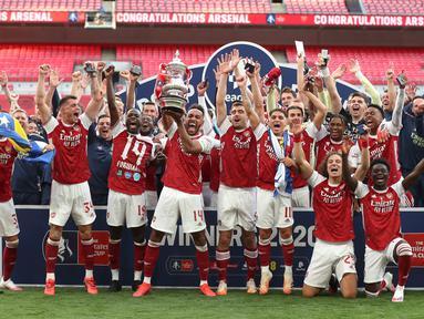 Para pemain Arsenal mengangkat trofi Piala FA setelah mengalahkan Chelsea pada pertandingan final Piala FA di stadion Wembley, London, Minggu (2/8/2020) dini hari. Arsenal juara Piala FA setelah menang dengan skor 2-1. (Catherine Ivill/Pool via AP)