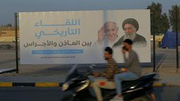 Sebuah papan reklame yang menampilkan gambar Paus Fransiskus dan ulama terkemuka Irak Ayatollah Ali al-Sistani, di Najaf, Irak, Kamis (4/3/2021). Pemimpin Tertinggi Umat Katolik Paus Fransiskus akan melakukan perjalanan bersejarah ke Irak pada Jumat (5/3/2021) waktu setempat. (AP Photo/Anmar Khalil)