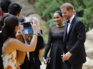Pangeran Harry dan Meghan Markle tiba menghadiri pemutaran perdana film The Lion King di London (14/7/2019). Duchess of Sussex tampil menawan dalam balutan gaun hitam dengan detail lebar di bagian bawah rok. (AFP Photo/Tolga Akmen)