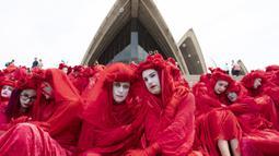 Aktivis yang terbagung dalam kelompok Red Rebels berunjuk rasa dalam demonstrasi protes iklim di Sydney (15/12/2019). Pengunjuk rasa melakukan aksi di depan landmark Gedung Opera Sydney menuntut pemerintah Australia menanggulangi asap yang menyebabkan masalah kesehatan. (AFP/Wendell Teodoro)