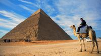 Seorang pria menunggang unta dengan latar belakang piramida Khafre yang berada di dataran tinggi Giza di pinggiran barat daya ibukota Kairo, Mesir (6/12). (AFP Photo/Mohamed El-Shahed)