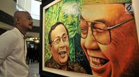 "Pengunjung melihat lukisan dalam pameran seni rupa ""Sang Maha Guru"" karya pelukis Nabila Dewi Gayatri di Jakarta, Kamis (22/11). Lukisan Gus Dur dipadu dengan berbagai tokoh dan ragam dimensi. (Merdeka.com/Iqbal Nugroho)"