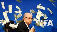 Komedian Inggris, Lee Nelson melempar uang kertas ke arah Sepp Blatter di markas FIFA di Zurich, Swiss. Tingkah Nelson itu dilakukan sebagai bentuk protesnya. (Reuters/Arnd Wiegmann)