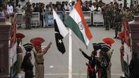 Tentara Pakistan (berseragam hitam) dan India dalam upacara rutin penurunan bendera di perbatasan (Reutes)