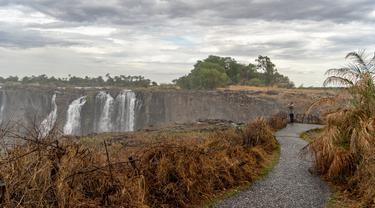 Seorang turis melihat Air Terjun Victoria yang megah di Zimbabwe (13/11/2019). Serangkaian gelombang panas telah mengeringkan sebagian besar vegetasi di sekitar situs warisan dunia UNESCO berukuran 108 meter dan lebar hampir 2 km dalam kekeringan parah. (AFP/Zinyange Auntony)
