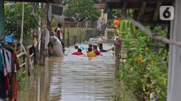 Anak-anak bermain saat banjir merendam Desa Karangligar, Kecamatan Telukjambe Barat, Karawang, Jawa Barat, Kamis (10/2/2021).  Banjir di Desa Karangligar akibat meluapnya sungai Citarum dan Cibeet membuat ratusan rumah terendam banjir dan ratusan hektar sawah. (Liputan6.com/Herman Zakharia)