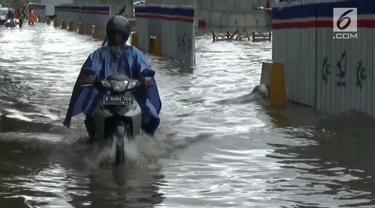 Hujan deras merendam ruas jalan D-I Panjaitan. Sejumlah kendaraan bermotor tidak dapat melewati area jalan.