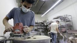 Pekerja menghaluskan bagian alat musik Oud di sebuah rumah produksi di Damaskus, Suriah (17/7). Berbeda dengan gitar, Oud tidak memiliki frets dan neck yang pendek. (AFP Photo/Louai Beshara)