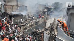 Petugas dibantu warga berusaha menjinakkan api yang melahap permukiman di Jalan Kebon Jeruk 13, Taman Sari, Jakarta Barat, Minggu (6/10/2019). Kebakaran diduga akibat anak bermain korek api. (merdeka.com/Iqbal Nugroho)