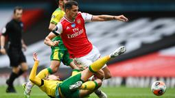 Gelandang Arsenal, Granit Xhaka, berebut bola dengan gelandang Norwich City, Tom Trybull, pada laga lanjutan Premier League pekan ke-32 di Emirates Stadium, Kamis (2/7/2020) dini hari WIB. Arsenal menang 4-0 atas Norwich City. (AFP/Shaun Botteril/pool)