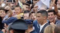 Cristiano Ronaldo saat menyapa suporter Juventus saat tiba di pusat layanan kesehatan Juventus (J-Medical), Turin, Italia, (16/7). Ronaldo akan mengenakan nomor punggung 7, seperti yang dikenakannya di Real Madrid. (AP Photo/Luca Bruno)