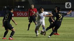 Pemain PSIS Semarang Riyan Ardiansyah (kanan) berebut bola dengan pemain Arema FC Hanif Abdurrauf Sjahbandi dalam pertandingan babak penyisihan Grup A Piala Menpora 2021 di Stadion Manahan, Solo, Selasa (30/3/2021). Arema FC kalah 2-3. (Bola.com/Ikhwan Yanuar)