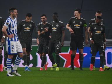 Gelandang Manchester United, Bruno Fernandes (tengah) berselebrasi usai mencetak gol ke gawang Real Sociedad pada leg pertama babak 32 besar Liga Europa di stadion Juventus, Turin (19/2/2021). Fernandes mencetak dua gol dan mengantar MU menang 4-0 atas Sociedad. (AFP/Marco Bertorello)