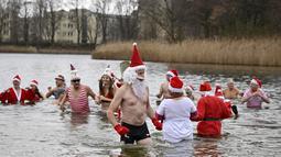 """Keseruan anggota klub renang """"Berliner Seehunde"""" (Berlin Seals) berendam di Danau Orankesee, Berlin, Minggu (25/12). Kegiatan yang sudah menjadi tradisi ini merupakan bagian dari perayaan tradisional Natal bagi warga Berlin. (Tobias SCHWARZ / AFP)"""