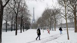 Aktivitas warga saat hujan salju di bawah Menara Eiffel di Paris, Prancis (7/2). Hujan salju yang sangat lebat membuat transportasi umum di paruh utara Prancis dan di Paris tidak dapat beroperasi. (AFP Photo / Thomas Samson)