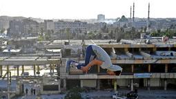 Pemuda Suriah berlatih parkour di Aleppo, Suriah utara, (7/4). Para pemuda memanfaatkan reruntuhan bangunan akibat perang menjadi tempat untuk melatih kelincahannya bermain Parkour. (AFP Photo/George Ourfalian)