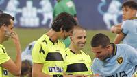 Kapten dan gelandang Beitar Jerusalem, Idan Vered (kanan) memeriksa jari-jari terawat wasit sepak bola transgender pertama Israel, Sapir Berman (tengah) sebelum Liga Premier Israel melawan Hapoel Haifa di Stadion Samy Ofer di kota Haifa, Senin (3/5/2021). (JACK GUEZ / AFP)