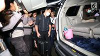 "Penyidik KPK memasukkan koper hitam ke dalam mobil seusai menggeledah rumah Ketua DPR Setya Novanto di Kebayoran Baru, Jakarta, Kamis (16/11). Mereka membawa sejumlah tas dan koper ""hardcase"" berwarna hitam dari rumah Setnov. (Liputan6.com/Johan Tallo)"