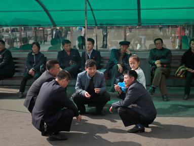 Sejumlah pria Korea Utara berbincang di luar supermarket di pusat kota Pyongyang, Korea Utara, (21/10).  (AP Photo / Dita Alangkara)