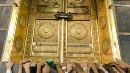Umat muslim memagang pintu Kakbah di Masjidil Haram, Mekah, Arab Saudi, Jumat (17/8). Kakbah menjadi kiblat umat muslim seluruh dunia saat melaksanakan salat. (AP Photo/ Dar Yasin)