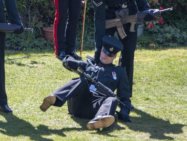 Seorang anggota The Rifles terjatuh menjelang pemakaman Pangeran Philip di luar Kapel St George di Kastil Windsor, Windsor, Inggris, Sabtu (17//4/2021). Prajurit yang tidak disebutkan namanya itu tampak tercengang saat dia jatuh ke tanah. (Arthur Edwards/Pool via AP)