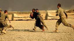 Tentara AS berlari membawa bola saat bermain American Football pada Thanksgiving di dalam pangkalan militer AS di Qayyara, selatan Mosul, Irak (24/141). (REUTERS/Thaier Al-Sudani)