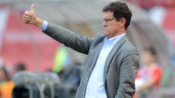 Fabio Capello pernah membuat aturan tak lazim untuk pemainnya saat melatih Timnas Inggris. Ia melarang pemainnya menggunakan sendal jepit, bermain game konsol, dan celana pendek dihadapan publik dengan alasan agar terlihat lebih professional. (Foto: AFP/Natalia Kolesnikova)