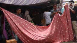 Pedagang mengukur kain dagangan di kawasan Pasar Cipadu, Tangerang, Selasa (2/3/2021). Pandemi Covid-19 membuat industri tekstil dan pakaian jadi mengalami pertumbuhan negatif 8, 8 persen sepanjang 2020 dengan kinerja ekspor yang berkontraksi 17 persen. (Liputan6.com/Angga Yuniar)
